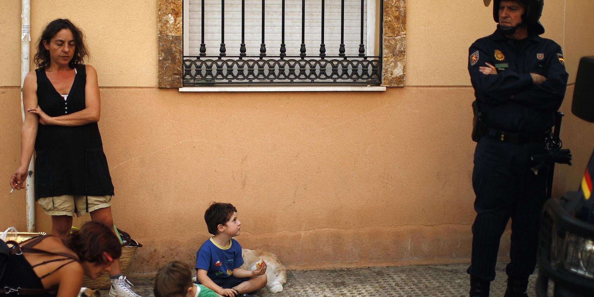 Gonzalez and her three and four-year-old children wait in a street with their dogs and belongings after Spanish riot police evicted them from an unoccupied building of flats in Malaga
